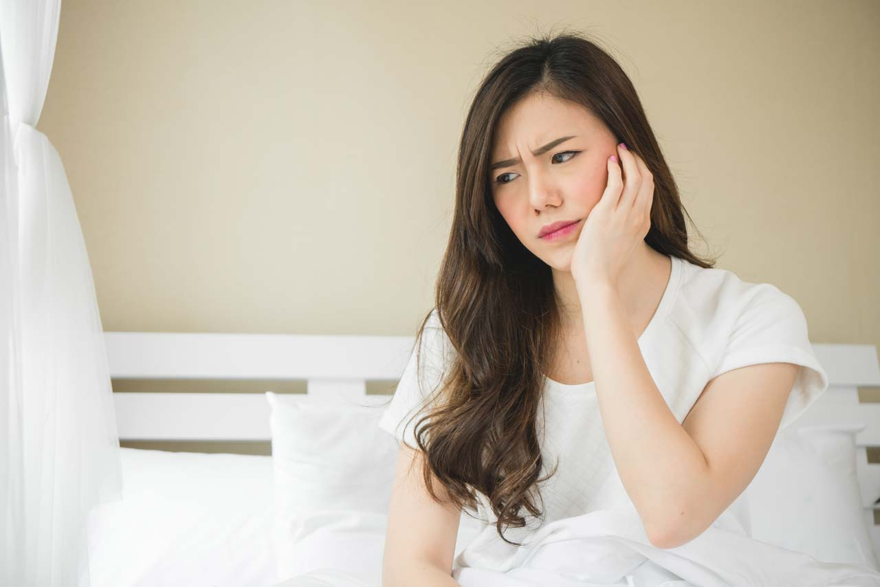 woman suffering from impacted wisdom teeth