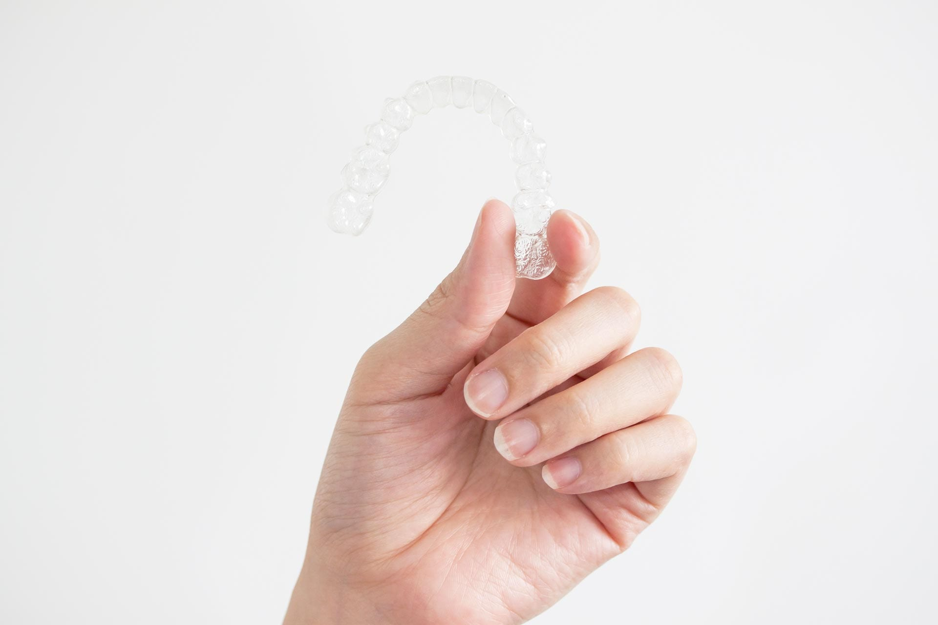 Hand holding onto an Invisalign clear aligner