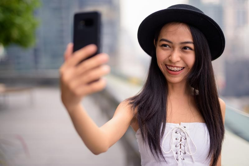 Braces lady holding phone to her face taking selfie | Braces treatment in singapore
