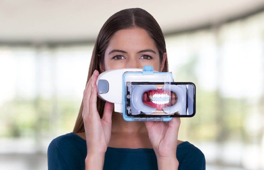 Woman using dental monitoring scanbox to scan and track her progress with Invisalign treatment