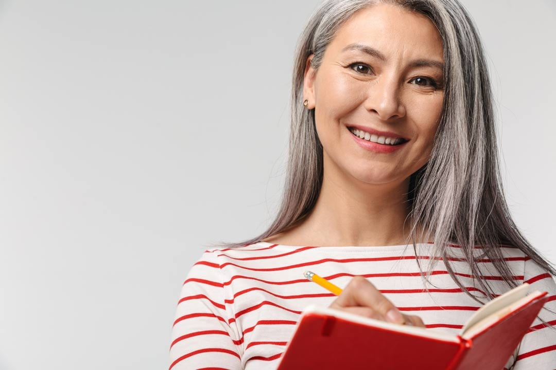 lady with dental implants smiling while writing on her red booklet