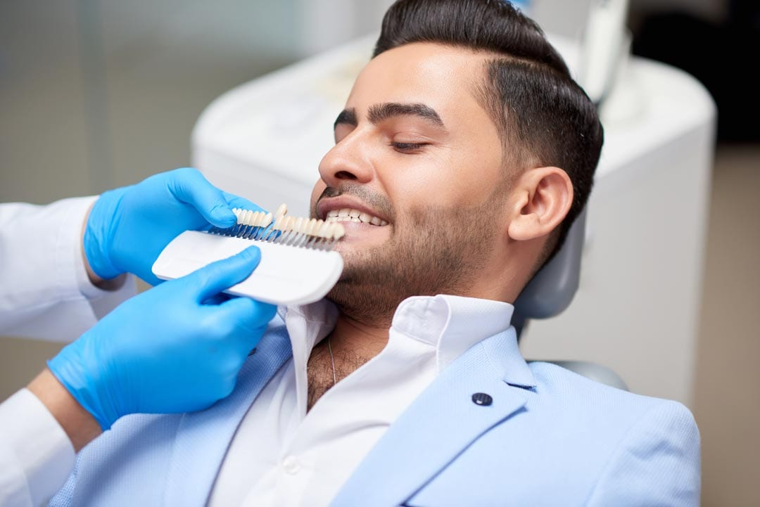 young man getting his teeth checked for the right tooth shade before getting dental veneers